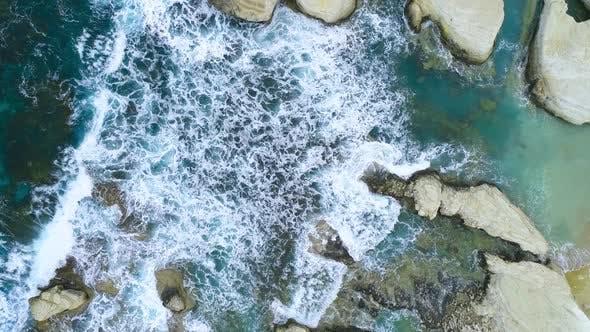 Charming Craggy Beach in Cyprus a Geological Wonder Sea Waves Splash Against Beach with Rocks