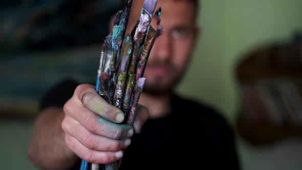 Artist Selecting and Dropping Paint Brushes on a Table