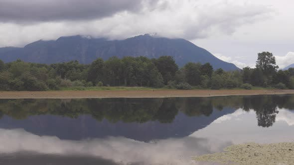 Cover Image for Cloudy Mountain Forest Timelapse Reflecting in Water - Snoqualmie, Washington USA Mill Pond