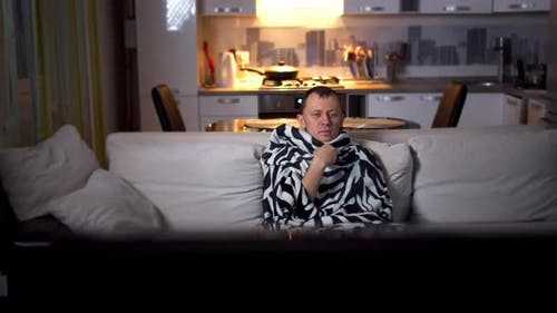 A Sick Man Sits on the Couch in the Evening and Watches TV, Camera Movement