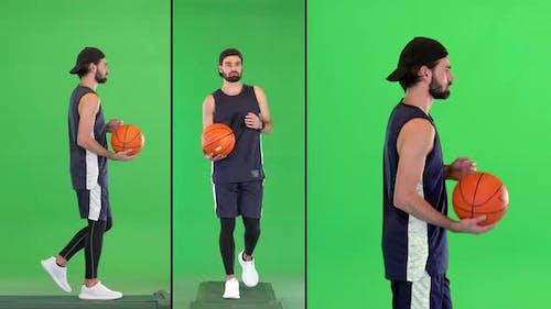 Attraktive Fröhliche Junge Fit Basketballspieler Gehen mit einem Ball in den Händen auf einem Green Screen