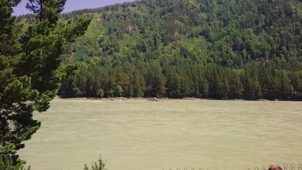 Aerial: Low Level Flying Over Mountain River with Rapid Current. Man Dressed in Shorts Looks at the