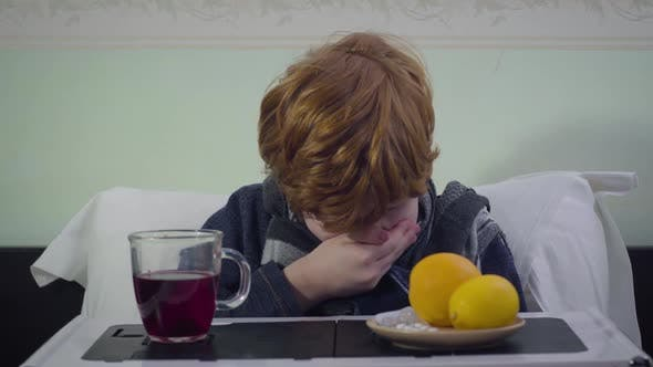 Thumbnail for Redhead Caucasian Boy Sneezing and Looking at Camera. Sick Redhead Child Sitting in Bed at Home