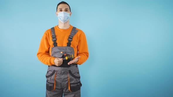 Young Professional Fixer with Covid 19 Mask and Screwdriver in Orange Clothes Isolated on Blue