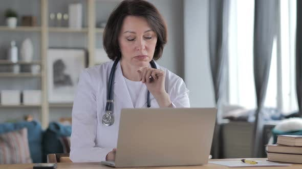 Thumbnail for Old Lady Doctor Thinking While Working on Laptop