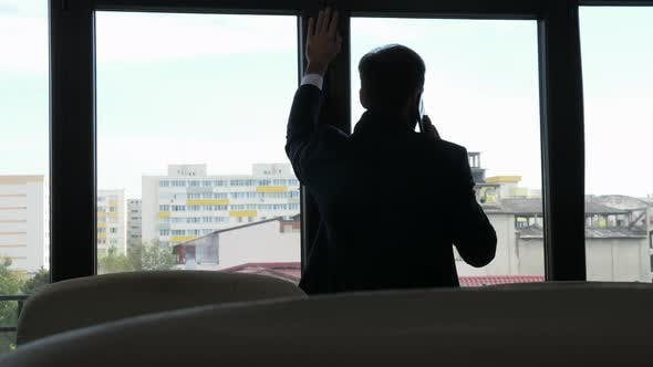 Troubled Businessman in Silhouette Talking on the Phone