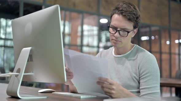 Thumbnail for Ambitious Guy Reading Document on Office Desk