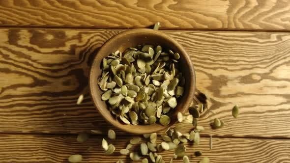 Thumbnail for Peeled pumpkin seeds fall into a wooden dish on a table