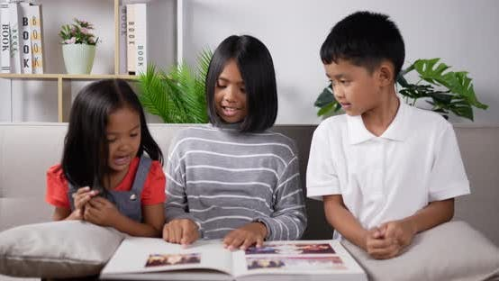 Three kids reading a book.