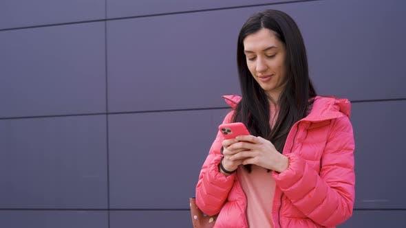 Thumbnail for wunderschöne Mädchen in rosa SMS auf Ihr Smartphone im freien