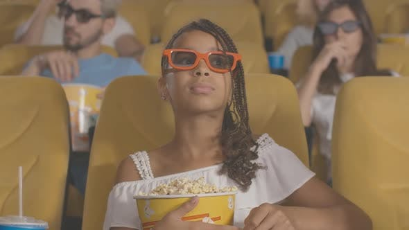 Thumbnail for Concentrated African American Girl with Afro Pigtails Sitting with Popcorn in Movie Theater and