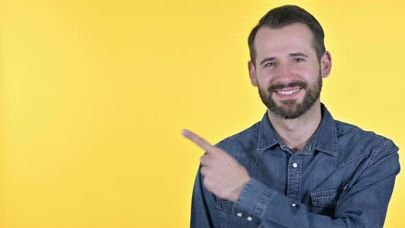 Thumbnail for Beard Young Man Pointing at Product, Yellow Background