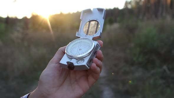 Thumbnail for Man Uses a Compass In The Woods At Sunset