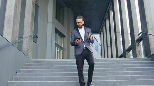 Businessman in Stylish Clothes Going Down the Steps while Leaving Office Center and Talking on Phone