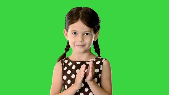 Little Girl in Polka Dot Dress Clapping Her Hands Looking at Camera on a Green Screen Chroma Key