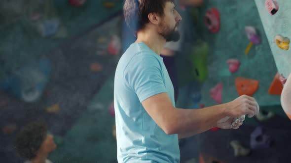 Young Man Using Chalk Powder Then Climbing Artificial Wall in Sports Center