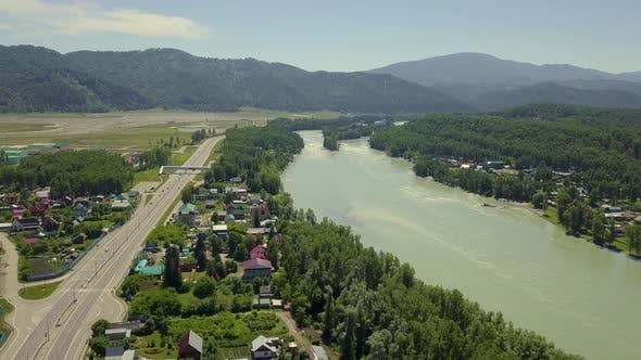 Aerial Flying Over Tourist Town in the Region of Mountains Mountain River and Fields