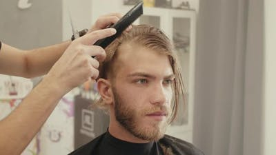 Combing blonde hair of a boy at the hairdresser