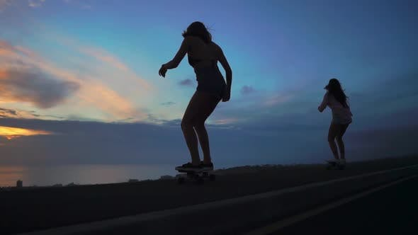 Cover Image for Two Girlfriend Girls in Shorts and Sneakers Ride Skateboards on the Slope Against the Beautiful Sky