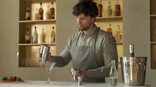 Bartender Pouring Cosmopolitan Cocktail in Martini Glass Decorates the Cocktail with Lime