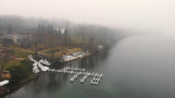 Aerial Flying Over the Lake in Heavy Fog and Cloudy Weather. The Embankment of the Lake on a Foggy