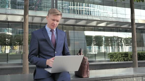 Thumbnail for Online Video Chat on Laptop by Businessman Sitting Outside Office