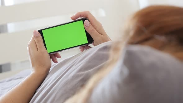 Modern smartphone with green screen display in female hands 4K 2160p 30fps UltraHD footage - In bedr