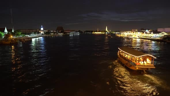 Thumbnail for Big cruise boat with illuminated colorful lights sailing across the river at night along cityscape