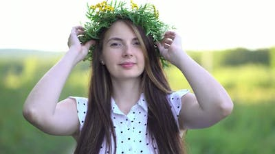 Woman Puts a Wreath of Wild Flowers on Her Head