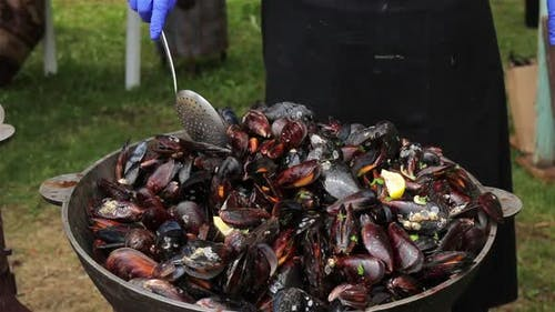 The process of preparing mussels in a large saucepan. Street food with seafood. Close-up.