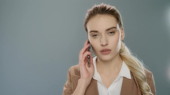 Thumbnail for Serious Business Woman Talking Mobile Phone on Gray Background