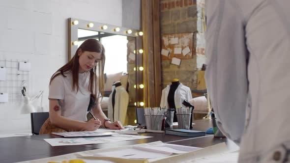 Female Fashion Designer Drawing Sketch in Sewing Workshop