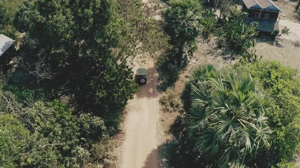 Drone Following a Vehicle on a Ground Colored in Brown Dirt