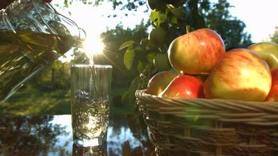 Apple juice and basket with apples.