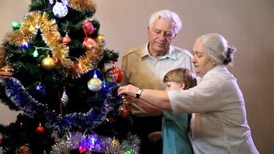 Little boy with grandmother and grandfather decorating christmas tree at home. Christmas,