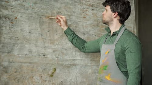 Concentrated Male Artist is Drawing on Easel in His Art Studio Side View