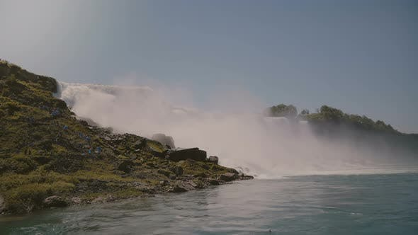 Thumbnail for Cinematic Shot of Tourists in Raincoats Watching Epic Wall of Water at Beautiful Famous Niagara