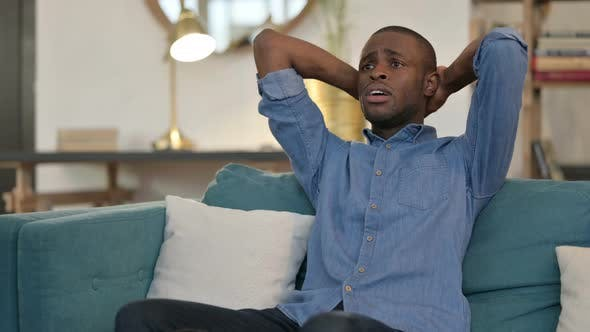 Anxious Young African Man Feeling Worried Sitting on Sofa
