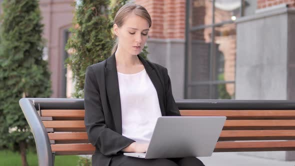 Cover Image for Businesswoman working on Laptop, Sitting Outdoor on Bench