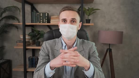 Thumbnail for Businessman in Headset and Face Mask Communicates By Conference Video Call. Confident Male Support