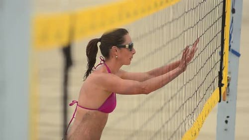 Extreme close-up selective-focus of women beach volleyball players at the net.