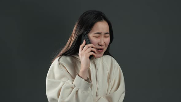 Thumbnail for Asian Girl Speaks on Phone and Sincerely Surprised By News She Heard