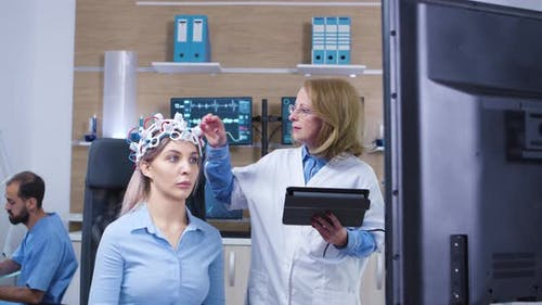 Dolly Shot of Female Doctor Checking Brain Activity of Her Female Patient