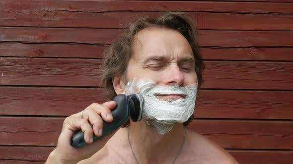 Thumbnail for Middle Age Man Shaves His Beard With Foam, Sitting In Yard, Outside.