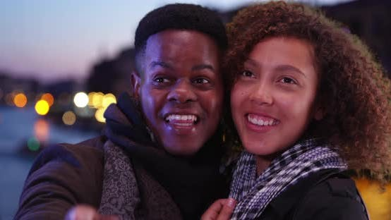Thumbnail for Happy black couple stand by the Grand Canal at night looking around in wonder