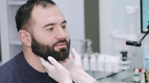 Otolaryngologin überprüft Lymphknoten und Rachen eines männlichen Patienten während der medizinischen Untersuchung in