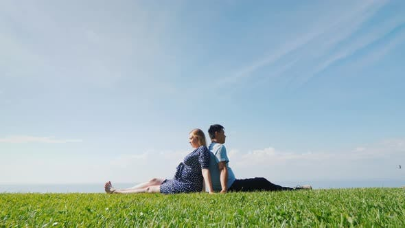 Thumbnail for Asian Man with a Pregnant Woman Are Resting in Nature in a Picturesque Place, Sit on the Green Grass