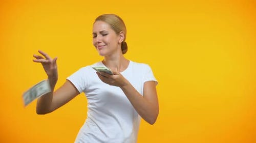 Carefree Woman Throwing Dollars Around, Rich Female Wasting Money, Consumerism