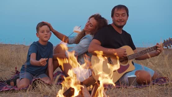 Thumbnail for Happy Family By Fire During Picnic on Beach in the Evening.