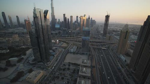 Slow Tilt View of Metropolitan Dubai City Center with Tall Skyscrapers and Busy Multi Lane Highway
